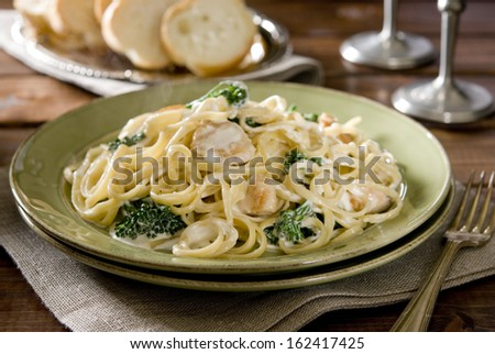 Plate of linguine with chicken, broccoli and Alfredo sauce. - stock photo