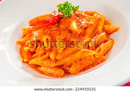 Plate of macaroni dish with tomato sauce. - stock photo
