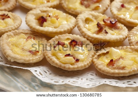 Plate of many mini bite size quiche appetizers - stock photo