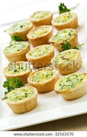 Plate of many mini bite size quiche appetizers - stock photo