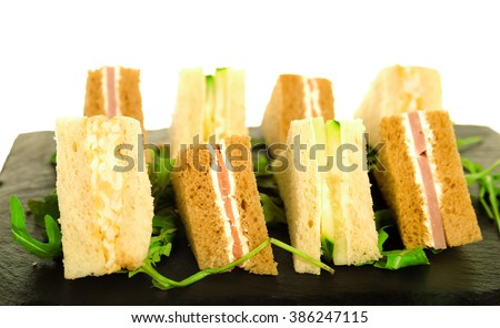 Plate of Many Mini Bite Size Sandwich Appetizers. Party Food, Finger Food, Sliders. Fresh Mini Bread with Cream Cheese, Smoked Salmon, Closeup. Sandwich Bacon and Vegetable for Meeting. - stock photo