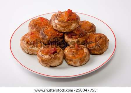 Plate of mushrooms stuffed with fried vegetables. Isolated over white background