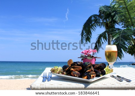 Plate of mussels on table on the beach - stock photo