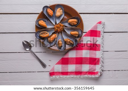 Plate of mussels with sauce - stock photo