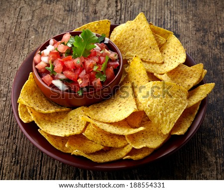 Plate of nachos and fresh salsa dip on wooden background - stock photo