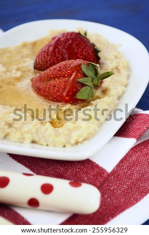 Plate of nutritious and healthy cooked breakfast oats with strawberries and honey in heart shaped bowl on dark blue rustic wood table, closeup. - stock photo
