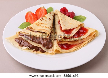 plate of pancake with chocolate and fruit - stock photo