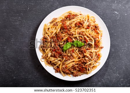 plate of pasta bolognese on dark background.
