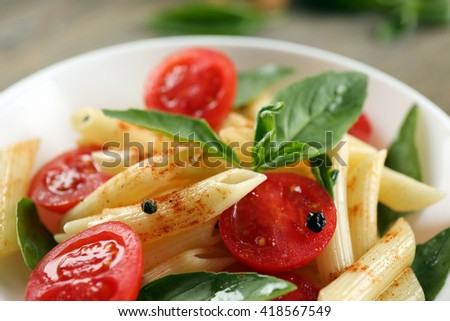 Plate of pasta with cherry tomatoes and basil leaves on table closeup - stock photo