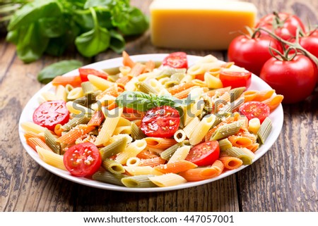 plate of pasta with tomato and green basil on wooden table