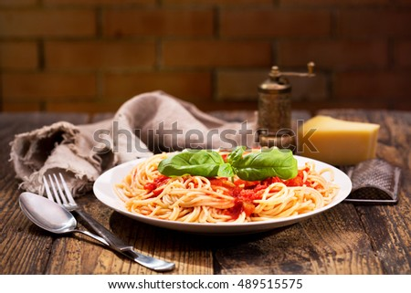 plate of pasta with tomato sauce and green basil on wooden table