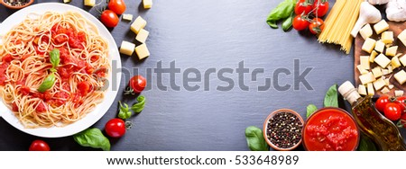 Plate of pasta with tomato sauce with ingredients for cooking on dark background. Top view with copy space, banner.