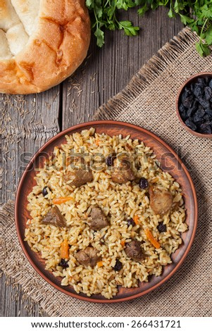 Plate of pilaf, traditional turkish spicy food with rice, fried meat, carrot onion and parsley. Served with fresh baked bread, raisins and vegetables. - stock photo