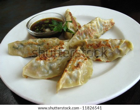 Plate of potstickers in restaurant - stock photo
