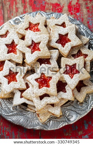 Plate of raspberry jam sandwich sugar Christmas cookies in star shaped cutout on a silver platter - stock photo