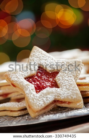 Plate of raspberry jam sandwich sugar Christmas cookies in star shaped cutout under the Christmas tree with defocused lights