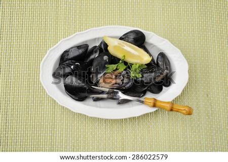 plate of raw shellfish with lemon - stock photo