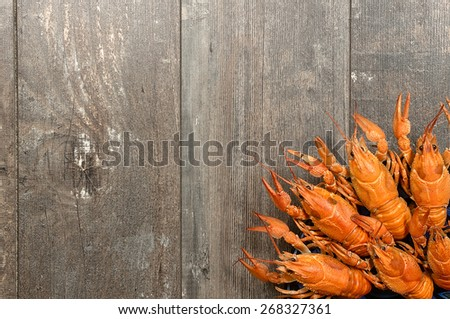 Plate of red crayfishes on old dark wooden table in left-bottom corner - stock photo