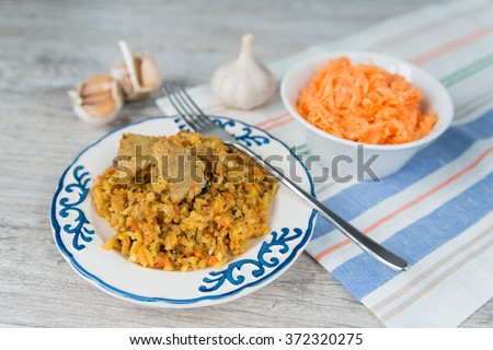 Plate of rice and meat national dish pilau with carrot salad - stock photo