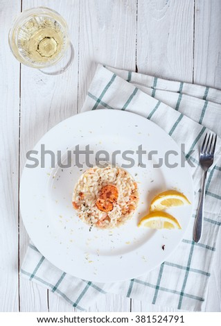 Plate of Risotto with shrimp and glass of white wine on white wood background - stock photo