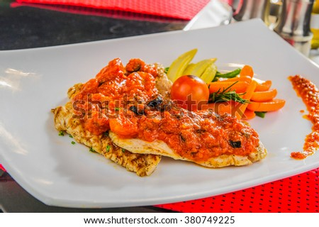 Plate of roasted chicken fillet with steamed vegetables and red sauce. - stock photo