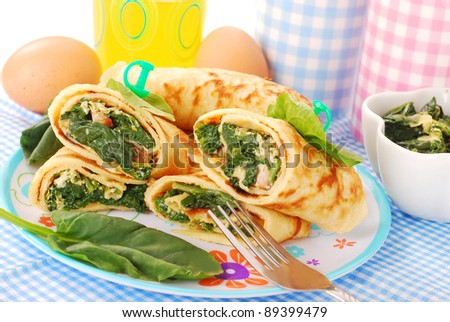 plate of rolled  pancakes stuffed with spinach ,bacon and eggs - stock photo