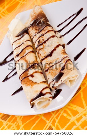 plate of rolled pancakes with chocolate syrup