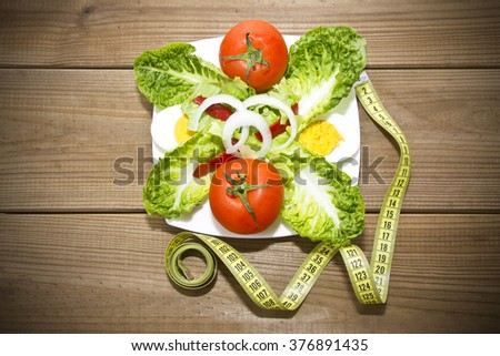plate of salad and tape measure on wood