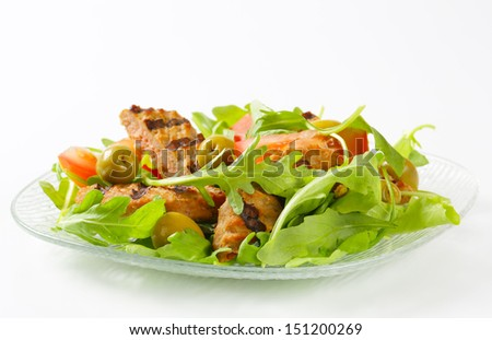 Plate of salad with grilled burger, olives and tomatoes