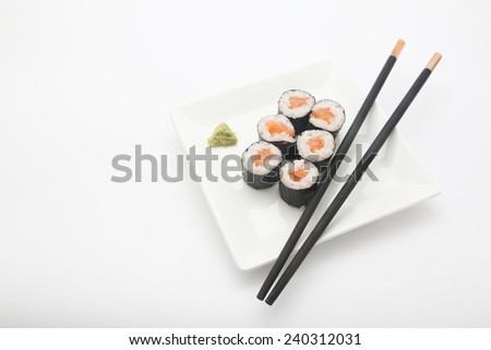 Plate of salmon maki sushi with chopsticks and wasabi