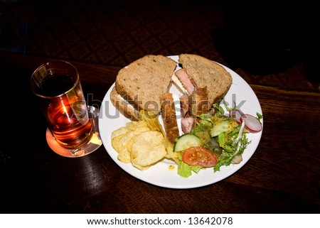 Plate of sandwiches, salad & crisps  and a glass on a polished table in a darkened pub - stock photo