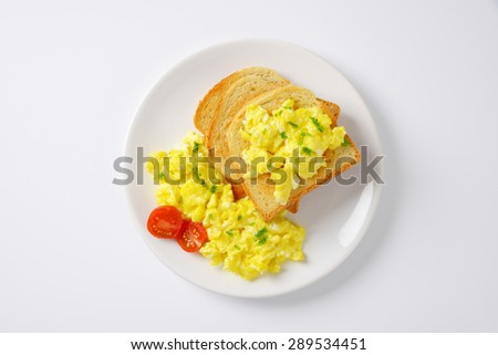 plate of scrambled eggs and slices of bread on white background - stock photo