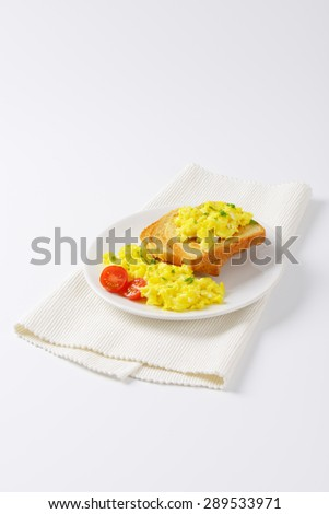 plate of scrambled eggs and slices of bread on white place mat - stock photo