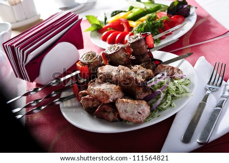 Plate of shish kebab cooked on skewers. - stock photo