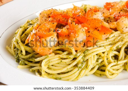 Plate of Shrimp in a tomato and pesto sauce on a bed of noodles - stock photo