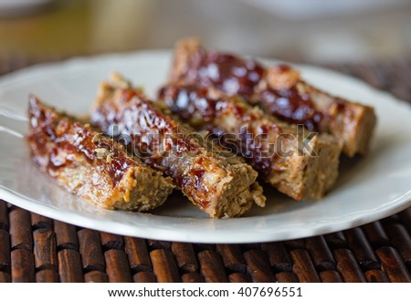 Plate of sliced homemade meatloaf with BBQ sauce topping - stock photo