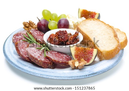 plate of snacks - sausage, bread, figs, grapes, nuts and dried tomatoes, close-up, isolated on white - stock photo