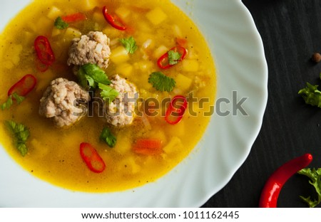 plate of soup with meatballs and vegetables on a dark wooden background