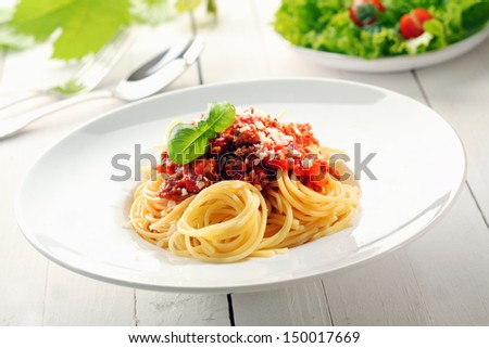 Plate of spaghetti bolognaise with a delicious sauce of tomatoes and minced beef garnished with basil - stock photo