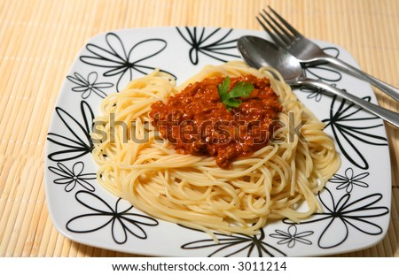 Plate of spaghetti with tomato bolognese sauce and a fork. - stock photo