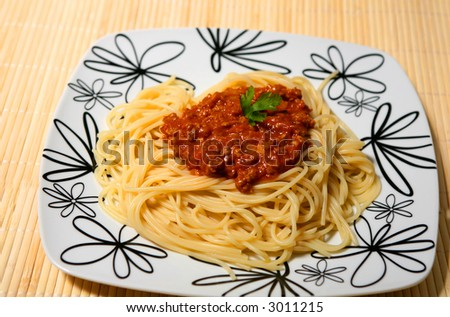 Plate of spaghetti with tomato bolognese sauce and a fork.