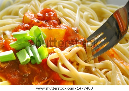 Plate of spaghetti with tomato sauce and a fork. - stock photo