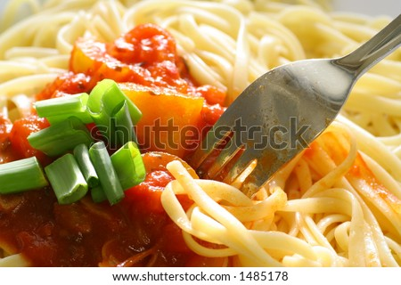 Plate of spaghetti with tomato sauce and a fork digging in. - stock photo