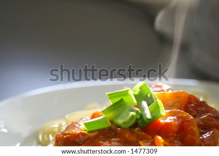 Plate of spaghetti with tomato sauce with steam coming up from the plate. - stock photo