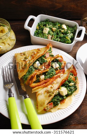 plate of spinach ,bacon and feta filled pancakes on wooden table - stock photo