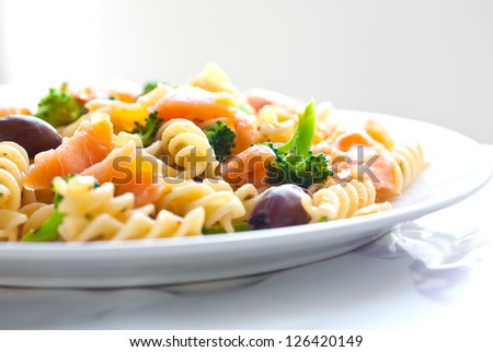 Plate of spiral pasta with smoke salmon and broccoli - stock photo