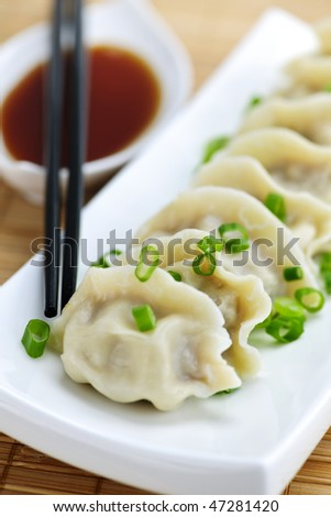 Plate of steamed dumplings with soy sauce and chopsticks - stock photo