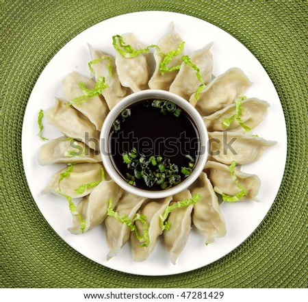 Plate of steamed dumplings with soy sauce from above - stock photo