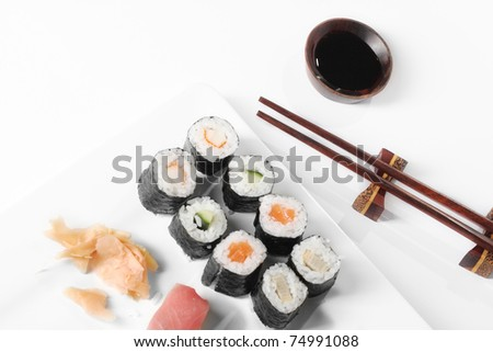 Plate of sushi rolls, with chopsticks at japanese restaurant - stock photo