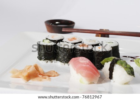 Plate of sushi rolls, with chopsticks at japanese restaurant